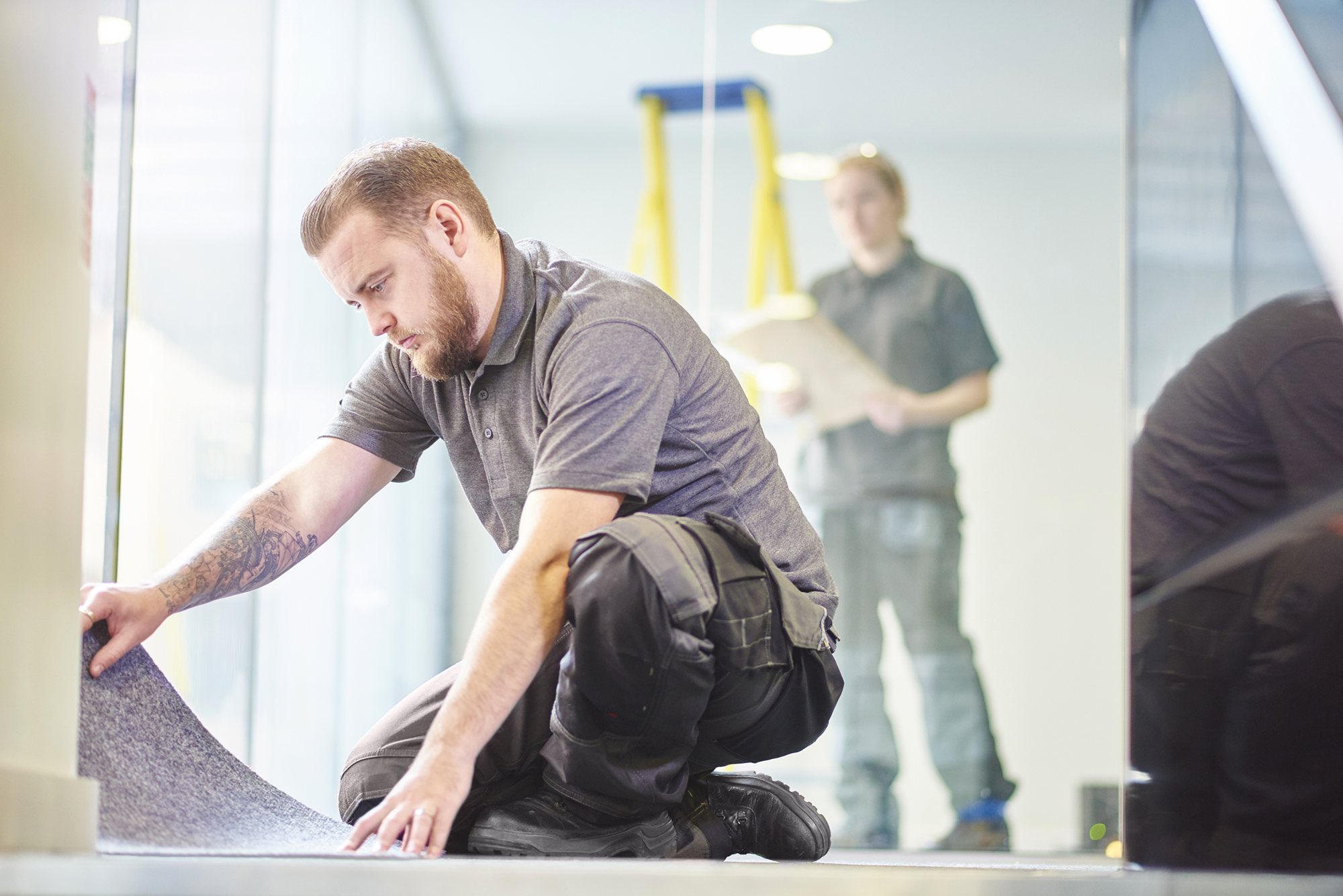 a male carpet fitter is installing carpet  in a modern office refurbishment. IN the background a female co-worker can be seen holding plans . They are wearing safety workwear.
