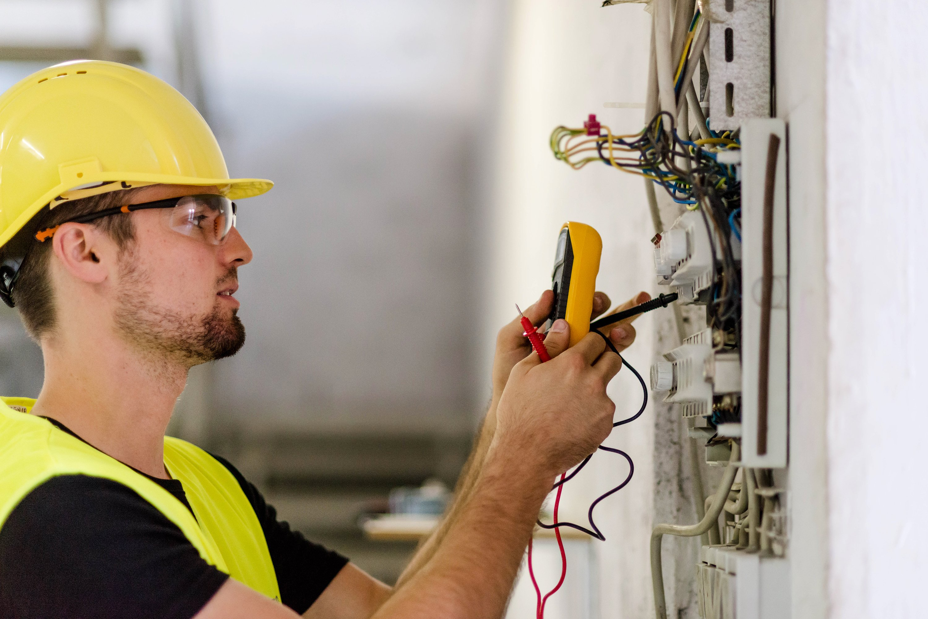 Electrician testing for voltage in a fuse box. He is wearing a protective vest,protective glasses and helmet